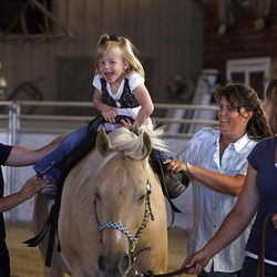 Brianna Heim, 5, rides with Valerie Duffin, left, and Cindy Becker while Andrea Smith leads at Buffalo Ranch in Farmington on Thursday as part of a therapeutic riding program.