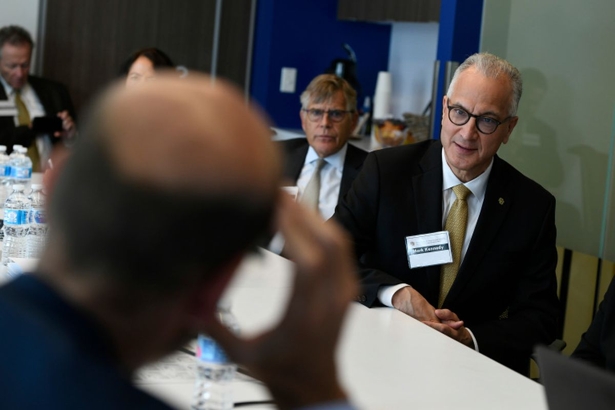University of Colorado President Mark Kennedy, wearing a suit, sits at a table with other people.