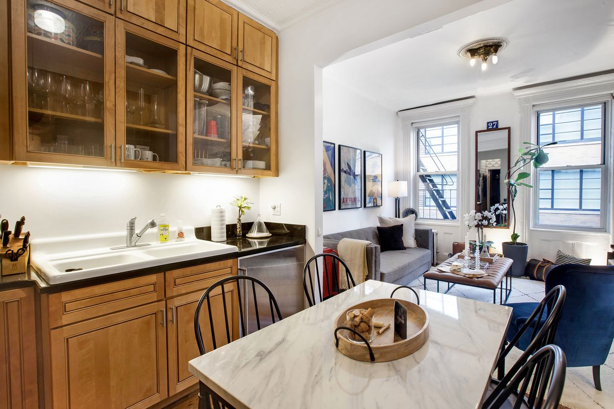 A kitchen with wooden cabinetry and a small dining table with four chairs.