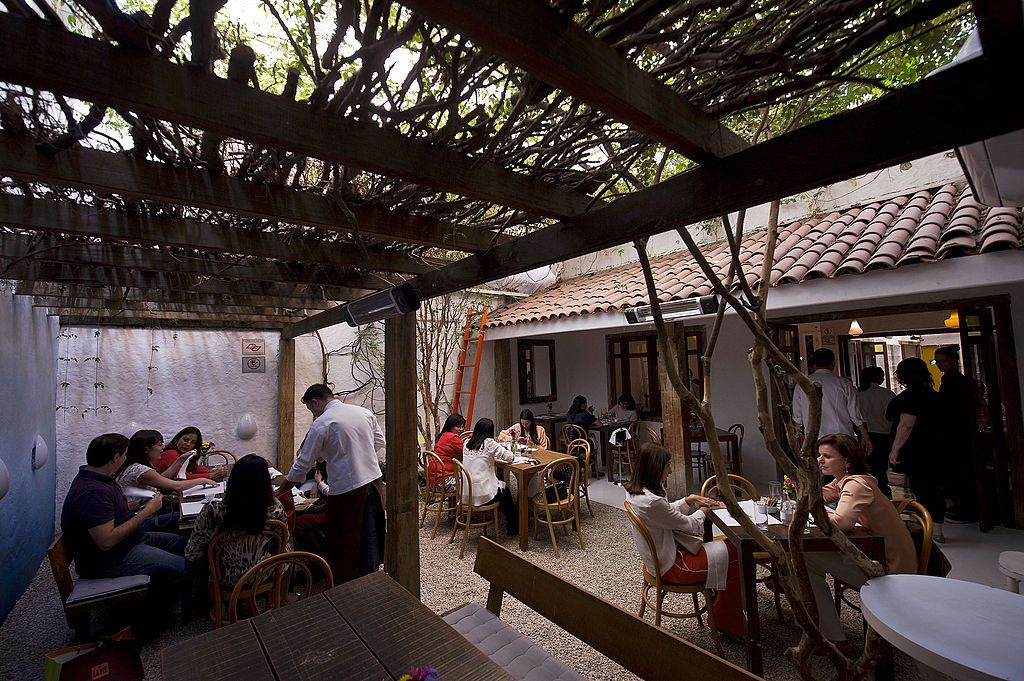Diners sit in outdoor seating area beneath a roof of branches that leads seamlessly into an open dining room beyond.