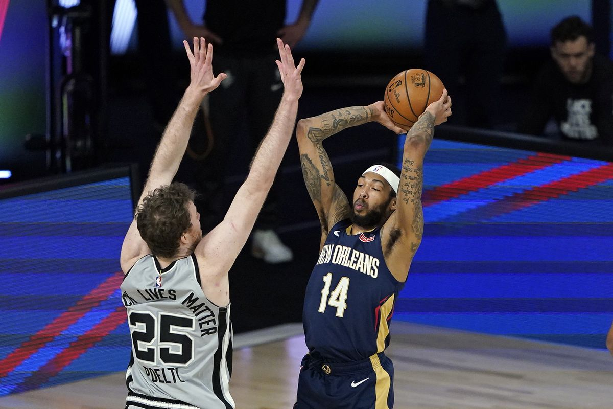 Brandon Ingram of the New Orleans Pelicans passes the ball over Jakob Poeltl of the San Antonio Spurs during the first half at HP Field House at ESPN Wide World Of Sports Complex on August 9, 2020 in Lake Buena Vista, Florida.
