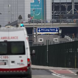 An ambulance heads to Zaventem airport as the blown out windows are seen, top right, following deadly attacks in Brussels, Belgium, Tuesday, March 22, 2016. Authorities in Europe have tightened security at airports, on subways, at the borders and on city streets after the attacks Tuesday on the Brussels airport and its subway system.