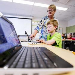 Substitute teacher Patrice Cullimore helps Tyler Muirbrook during class Monday, March 30, 2015, at Endeavour Elementary in Kaysville.