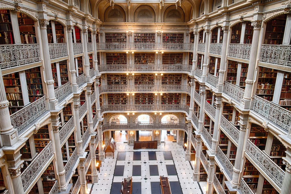 The interior of the Peabody Library. There are multiple levels with rows of bookshelves that contain many books. The balconies and columns are white. The floor has blue and white tiles.