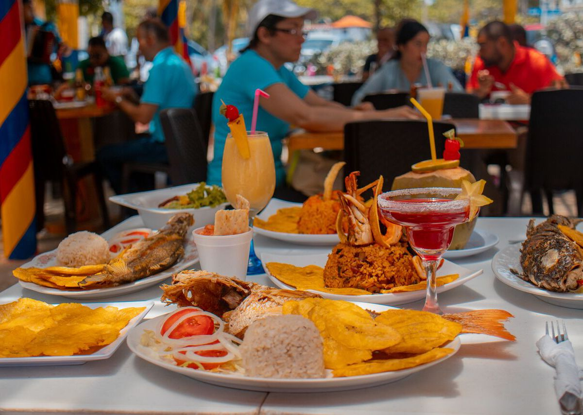 An outdoor table is topped with several including fried fish, fried plantains and cocktails, with diners blurred in the background sitting at outdoor tables