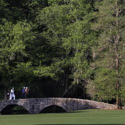 Tiger Woods, left, walks across the Byron Nelson Bridge with Mark O'Meara on the 13th fairway during a practice round for the Masters golf tournament Monday, April 2, 2012, in Augusta, Ga.