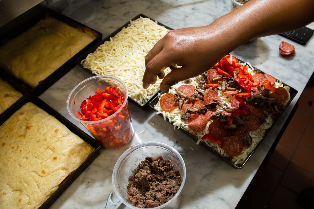 A hand reaching for red peppers and crumbled meat to put on a square pizza with cheese before baking