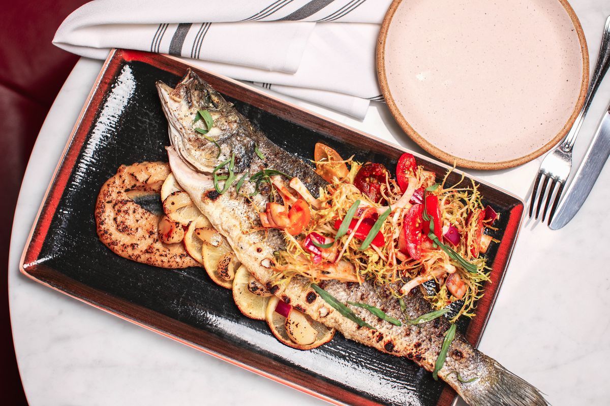 A whole piece of grilled fish on a plate with herbs on the side