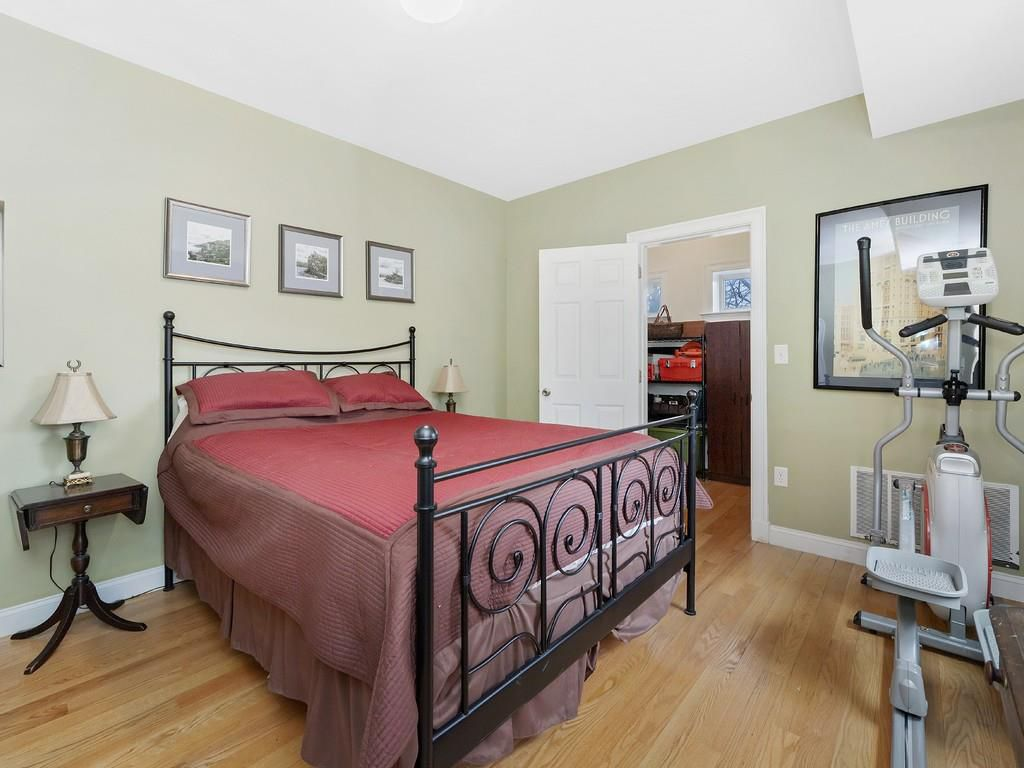 Bedroom with a bed in a wrought-iron frame next to a step-exercise machine.