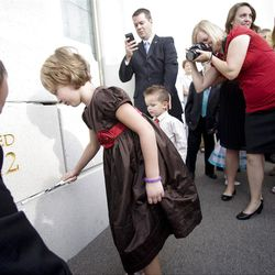 Aliya Purcell tries her hand at putting mortar around the cornerstone. About 200 took part in the ceremony at the Brigham City Temple prior to the dedication Sunday, Sept. 23, 2012.