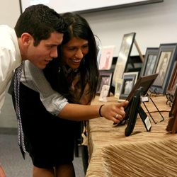 Allan and Elizabeth Escobar look at photos during a memorial service for Janie Thompson, the founder of BYU's internationally touring Young Ambassadors, at the BYU multi-stake center in Provo on Saturday, June 8, 2013.