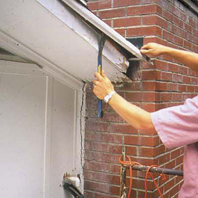 Man Removes Shingle Mold With Pry Bar To Repair Soffit
