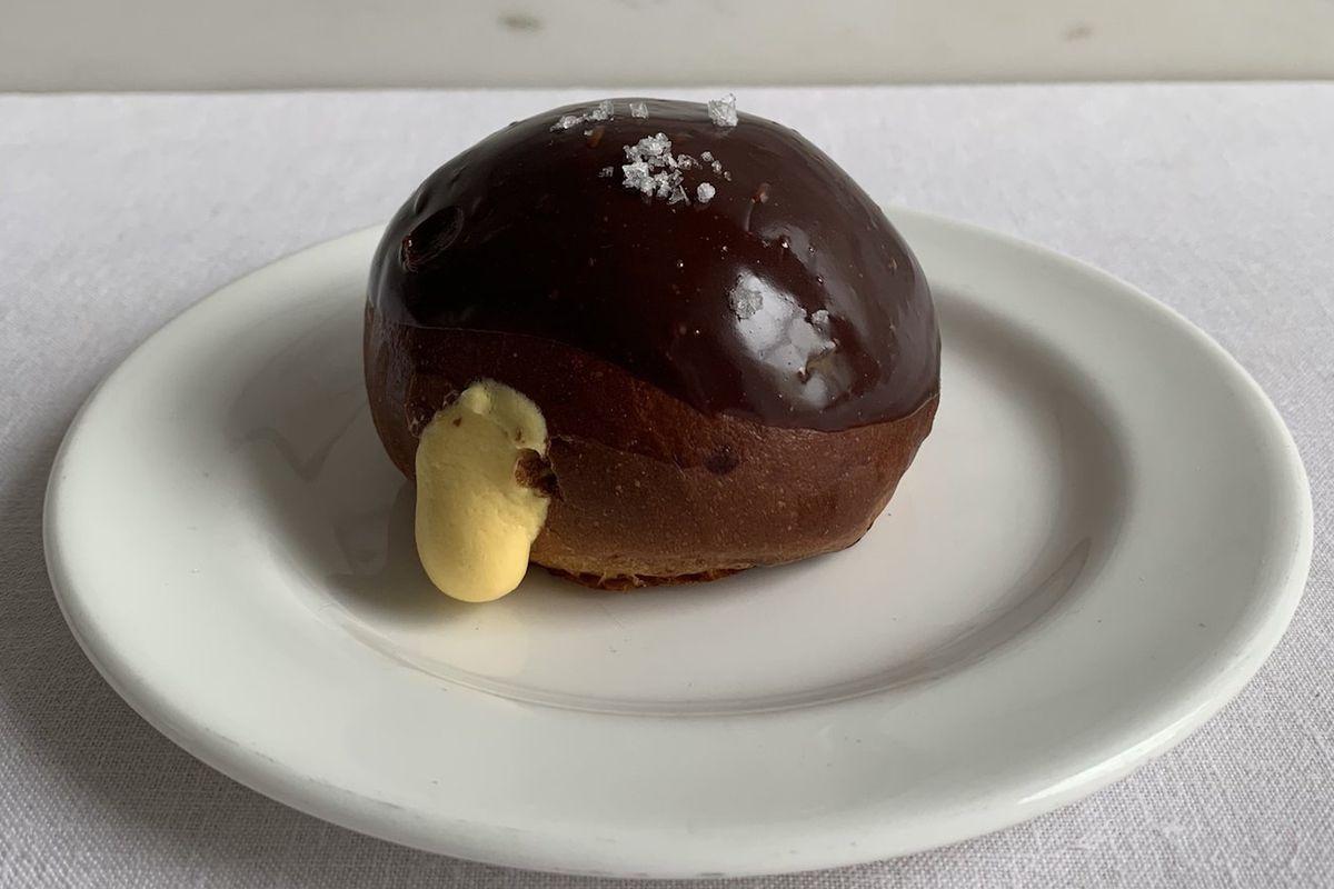 A coconut custard and chocolate bun on a white plate