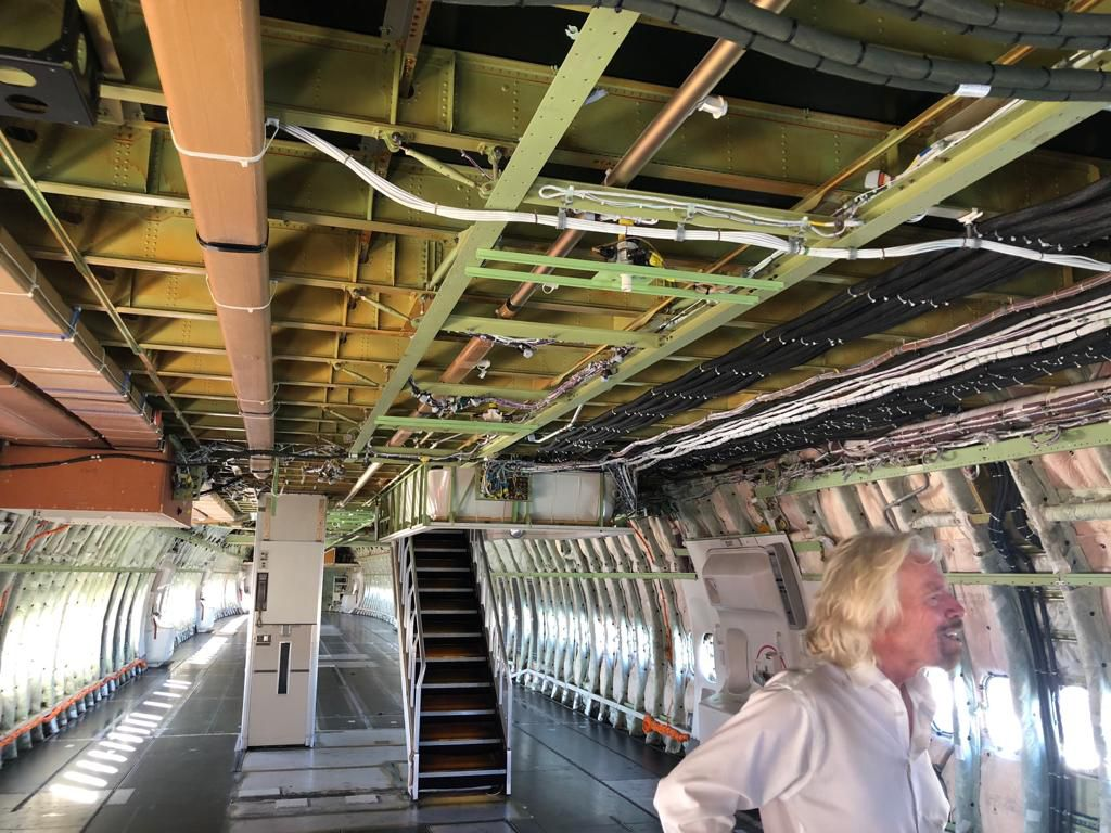 man standing inside mostly empty airplane