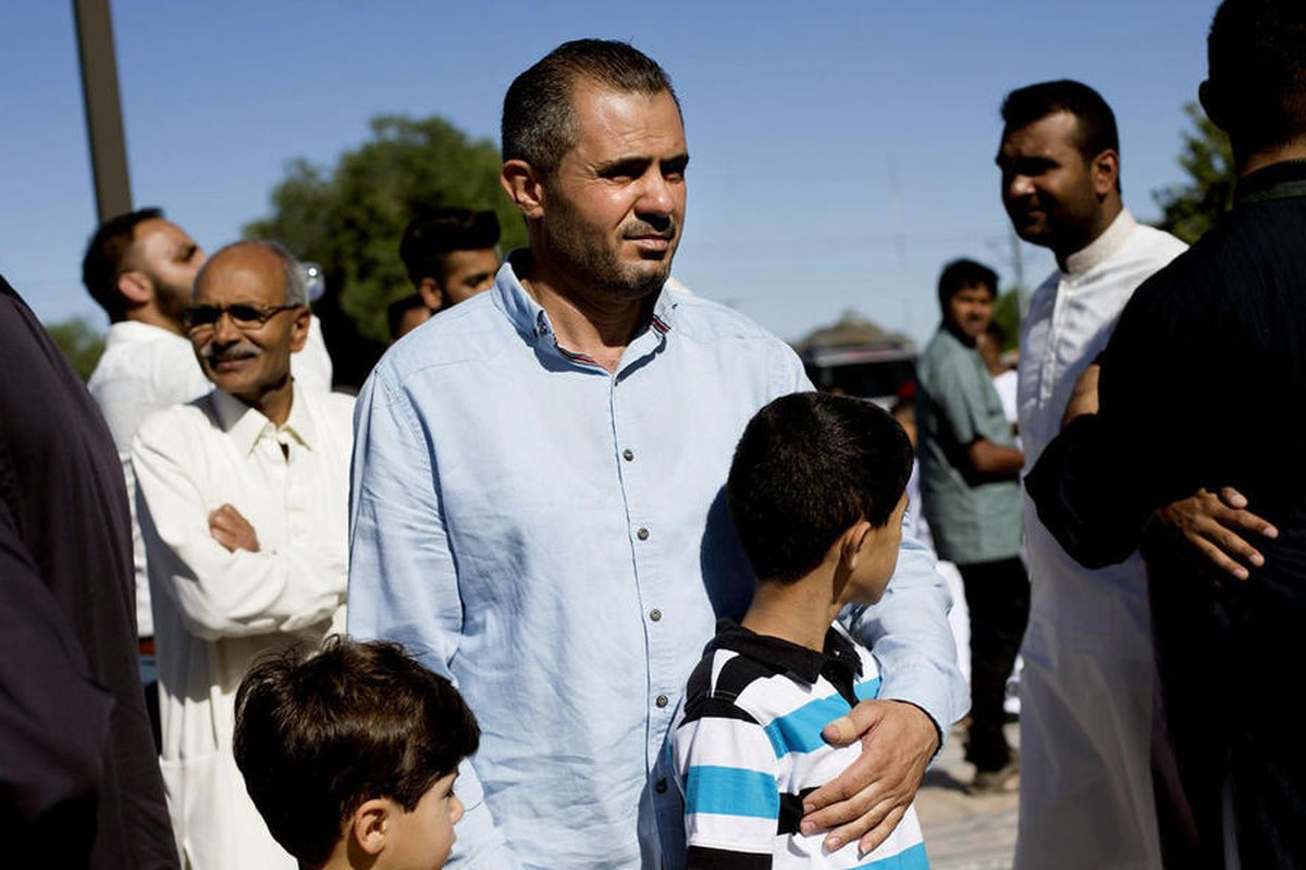 """Malek Hamad holds his sons Eslam and Abdullah while searching for his wife""""™s cousin, after praying at the end of Ramadan, at the Khadeeja Islamic Center in West Valley City, June 25, 2017. The Hamads had been in the United States for only a month as of t"""