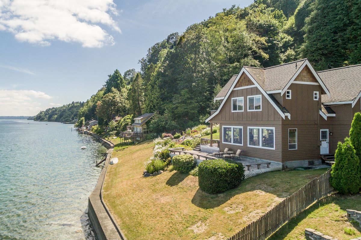 A brown house on a grassy waterfront