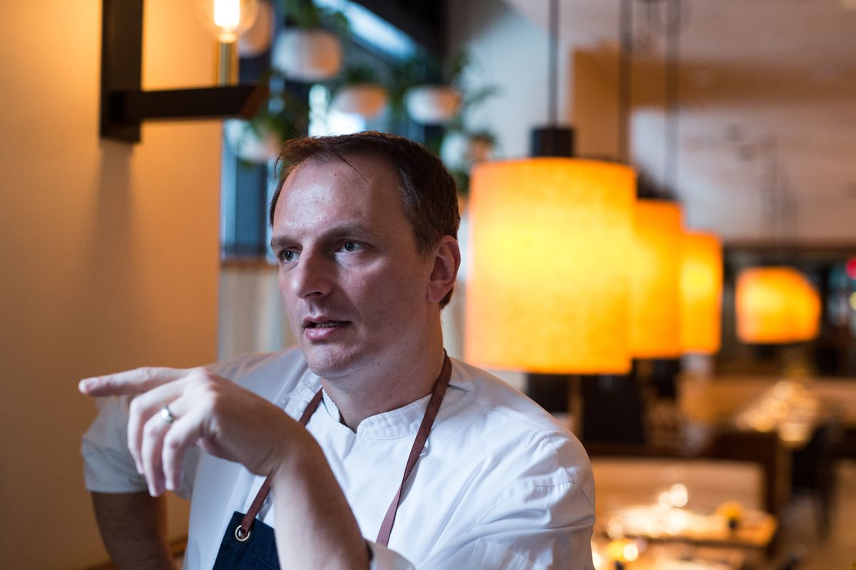 A man in a chef's apron sits in front of a row of warm lamps. He points a finger off-screen.