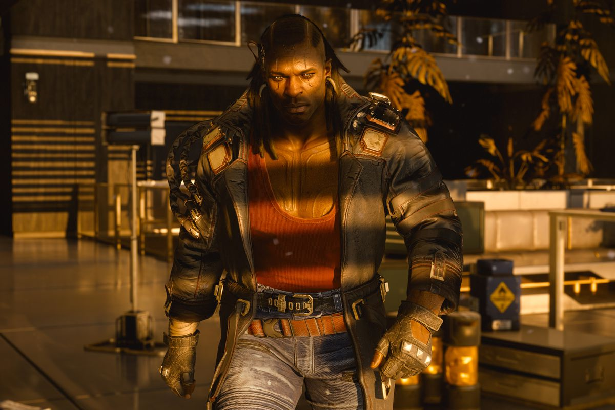 a musclebound black man in a red tank top, blue jeans, and a brown leather jacket walks through shadow