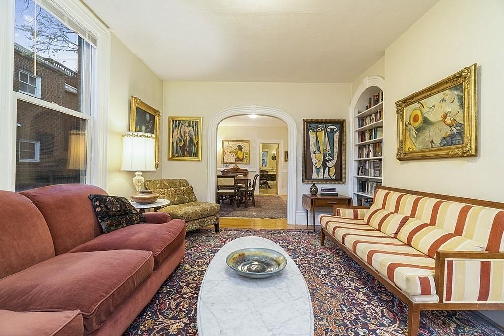 A spacious living room with two couches facing each other, and then a large opening leads from the room.