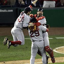 Boston's Doug Mientkiewicz, left, Jason Varitek and Keith Foulke (29) celebrate the Red Sox's sweep of St. Louis on Wednesday.