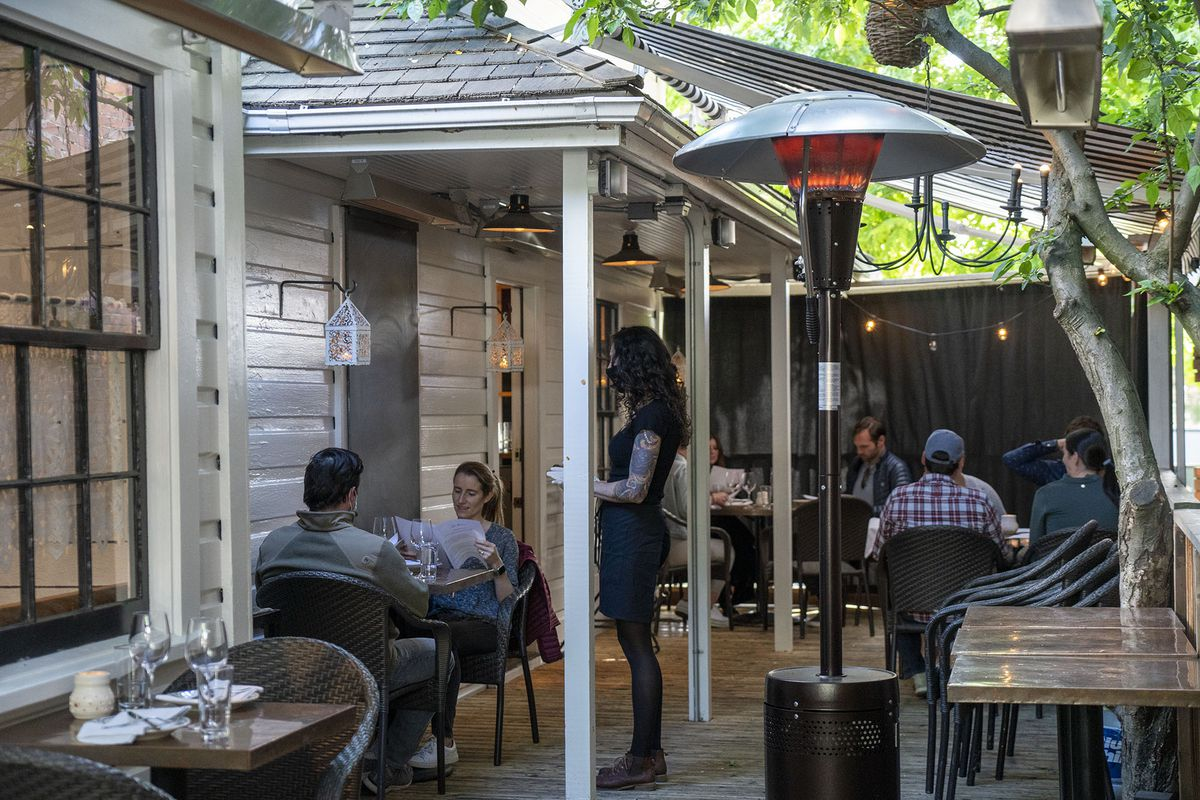 The patio at San Fermo in Ballard, where there were spaced out tables outside and a masked server attending to diners
