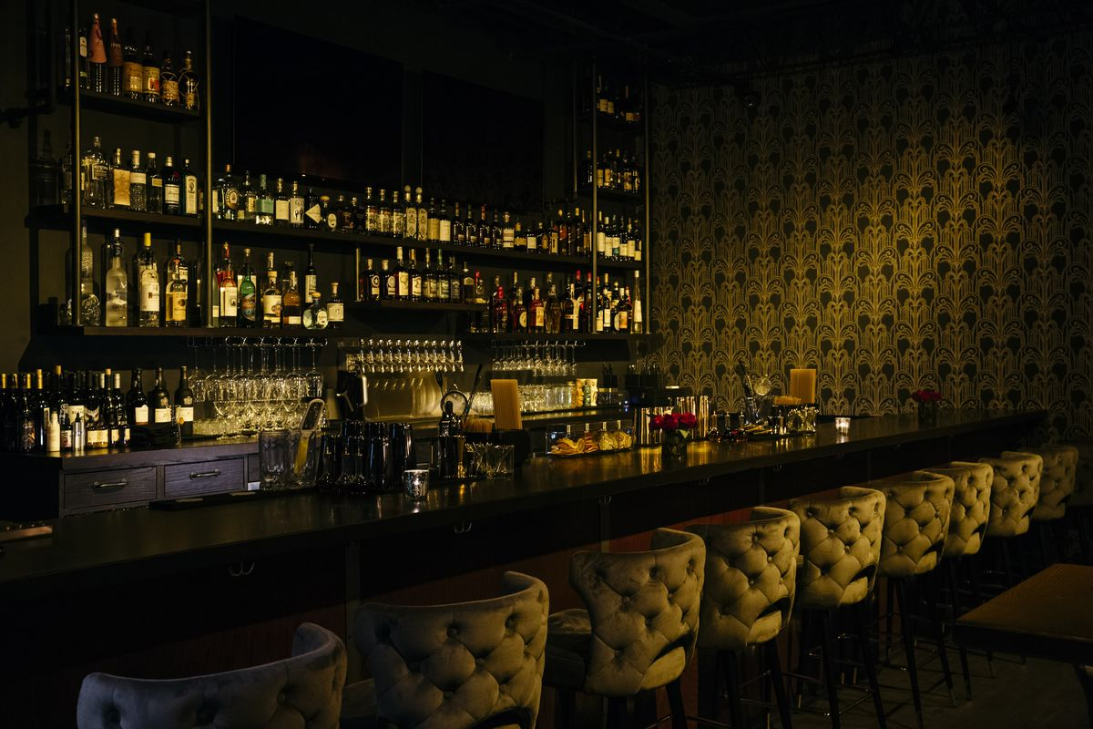 A dimly lit bar corner with textured gold wallpaper and plush-backed stools lining bar