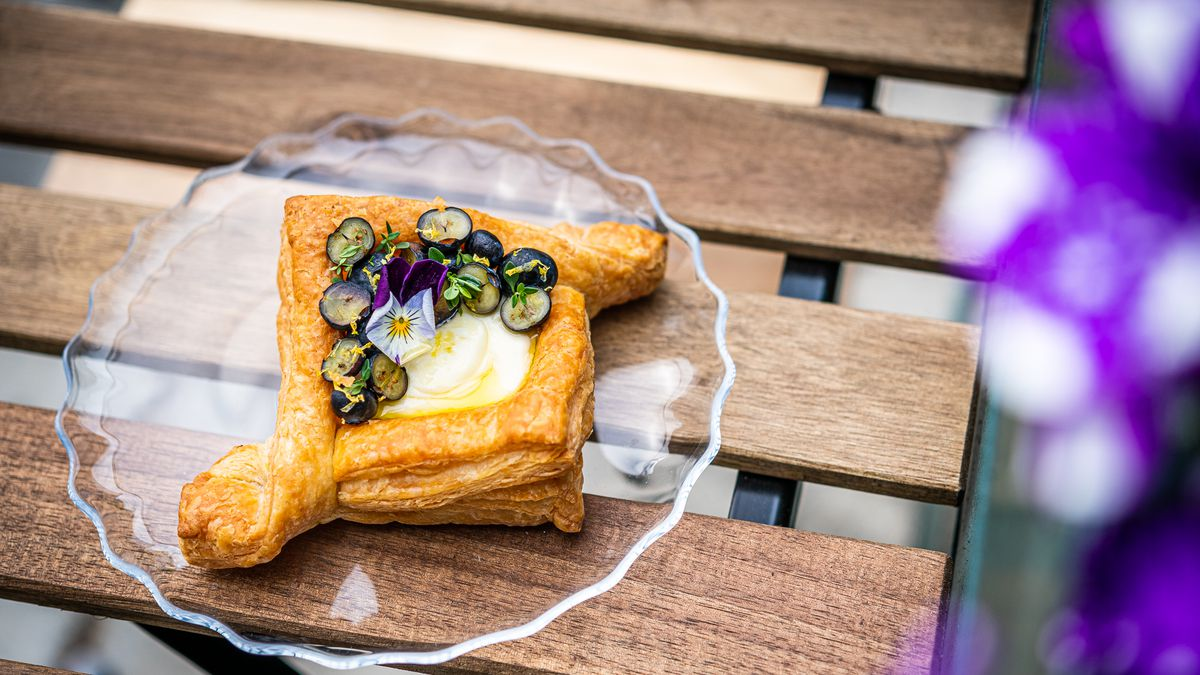 A danish from Little Food Studio with purple and white flowers and sliced blueberries