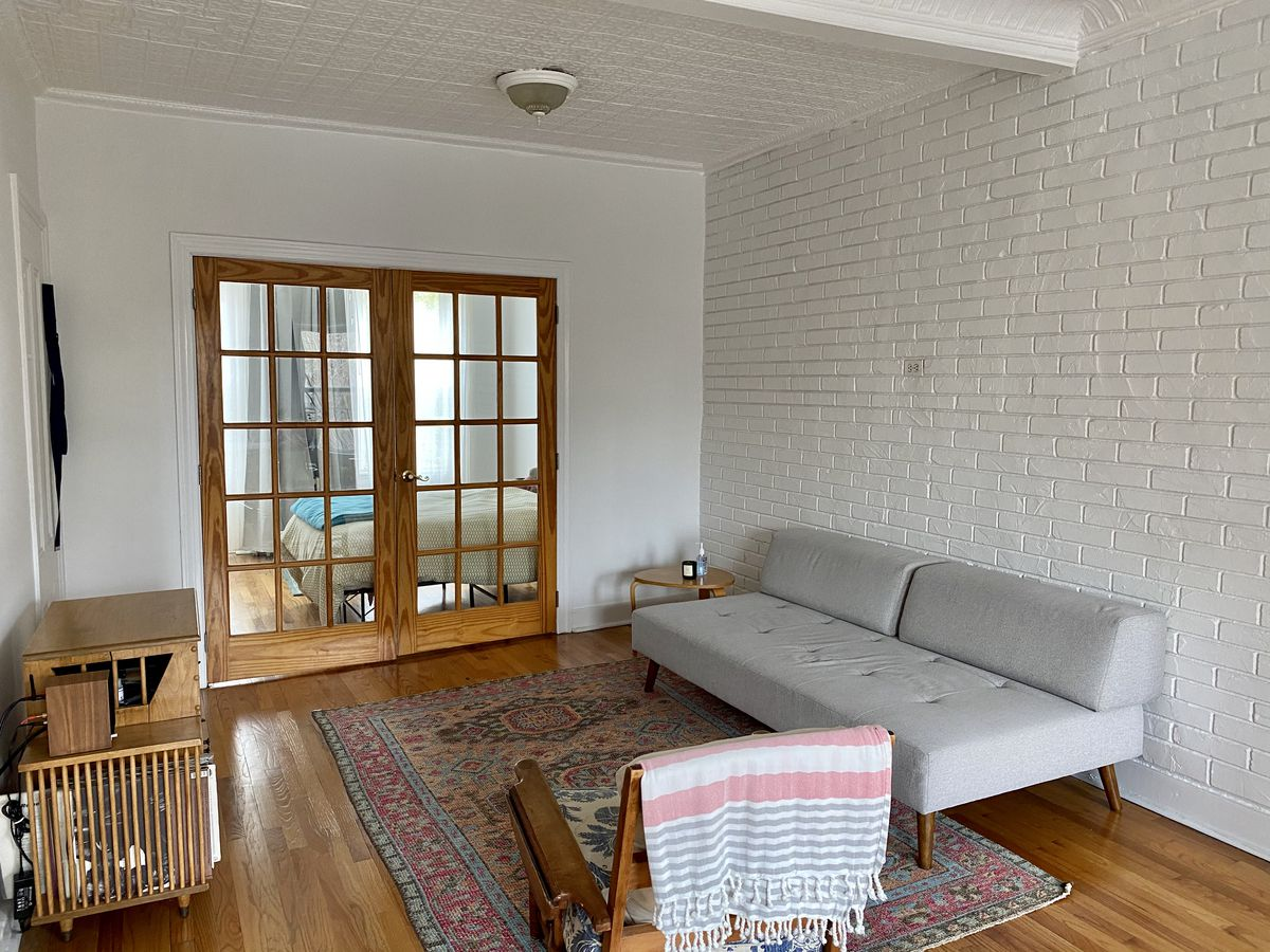 A living area with hardwood floors, white exposed brick, a grey couch, and French doors that lead to a bedroom.