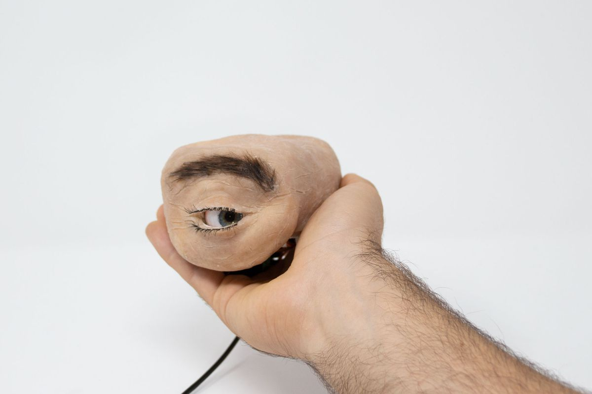 A person's hand tenderly holds a piece of synthetic meat with an eyeball in it, and glances to the right.  There is a wire coming from behind.