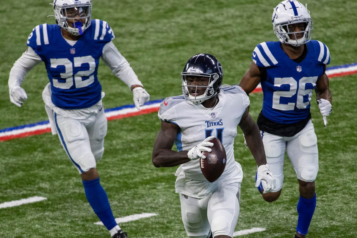 Tennessee Titans wide receiver A.J. Brown (11) runs with the ball while Indianapolis Colts free safety Julian Blackmon (32) and cornerback Rock Ya-Sin (26) defend in the first half at Lucas Oil Stadium.