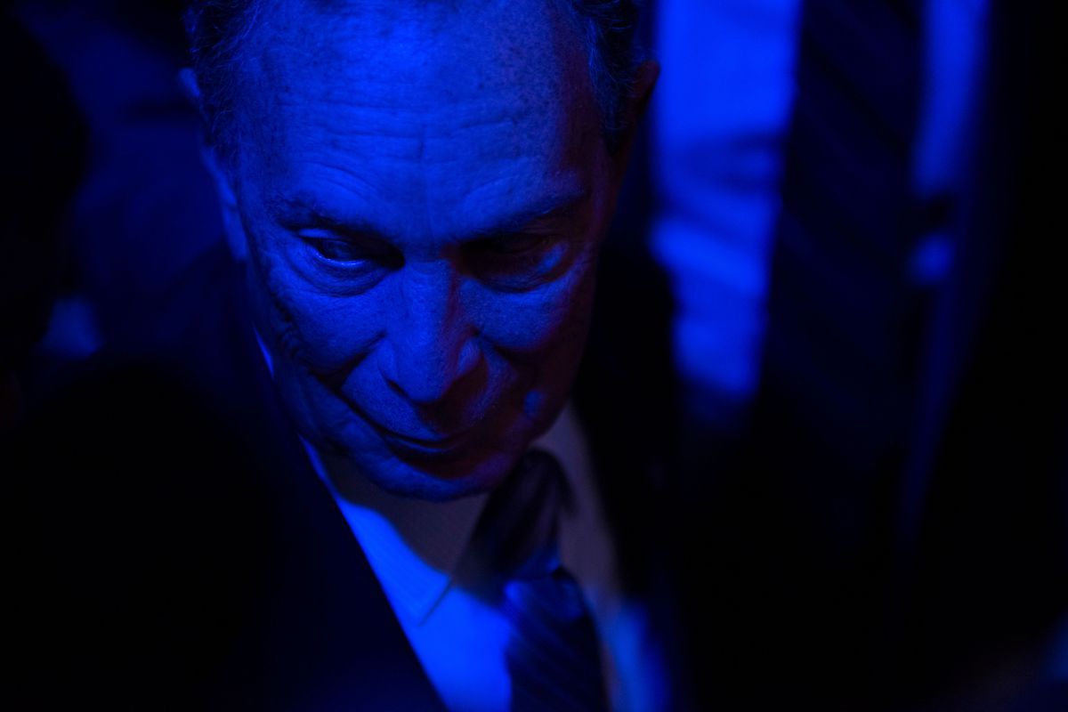 Bloomberg, bathed in blue light, speaks to supporters.