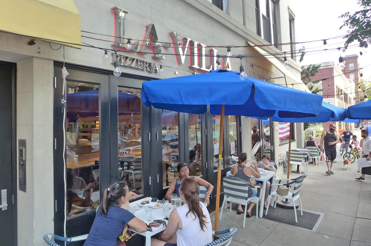 A couple of tables with guests on the sidewalk and blue umbrellas overhead.
