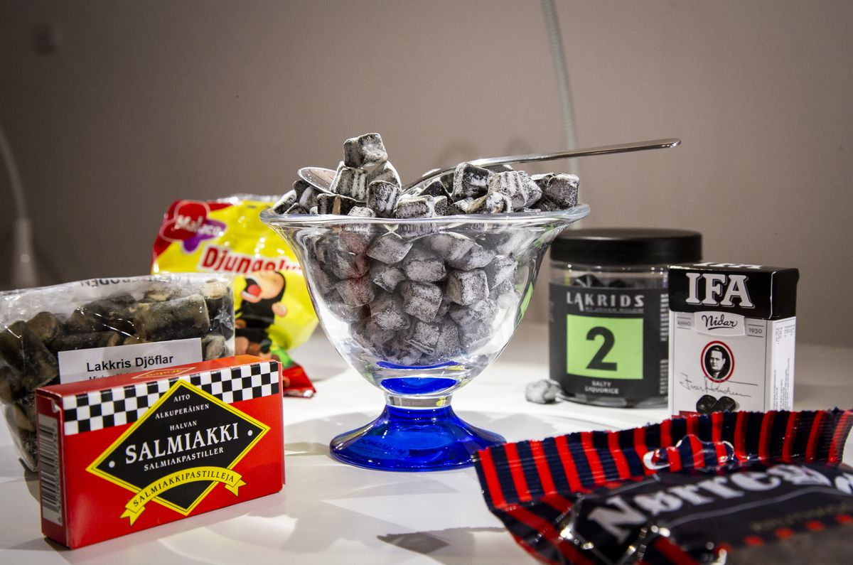 A bowl of licorice surrounded by containers of licorice