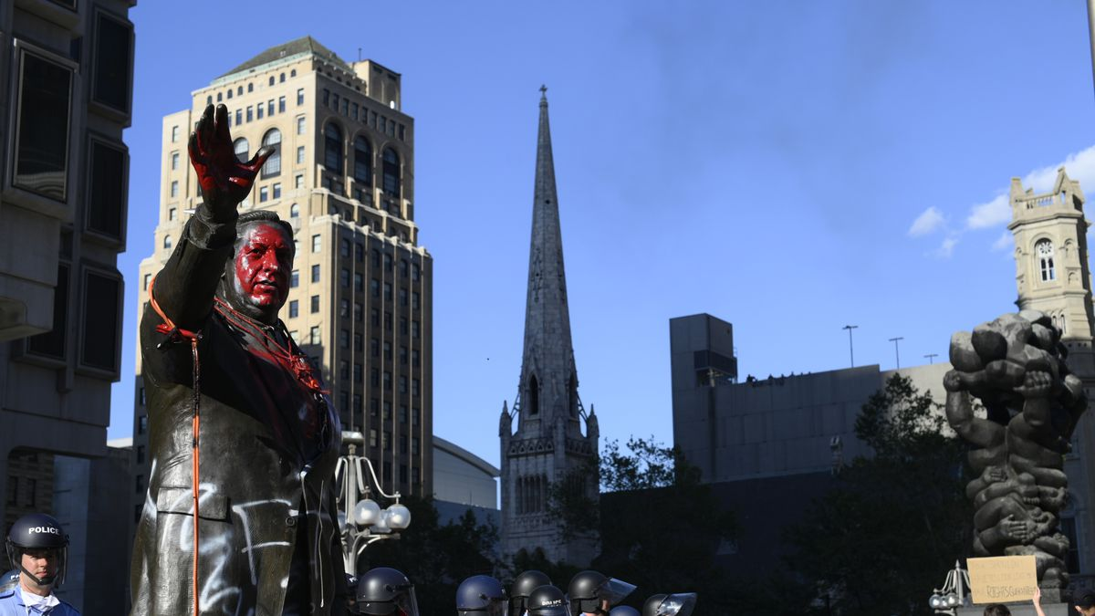A bronze statue with red paint splashed over its face and a sea of cops protecting it. This shows how racist statues and monuments related to slavery and colonialism have been targeted.