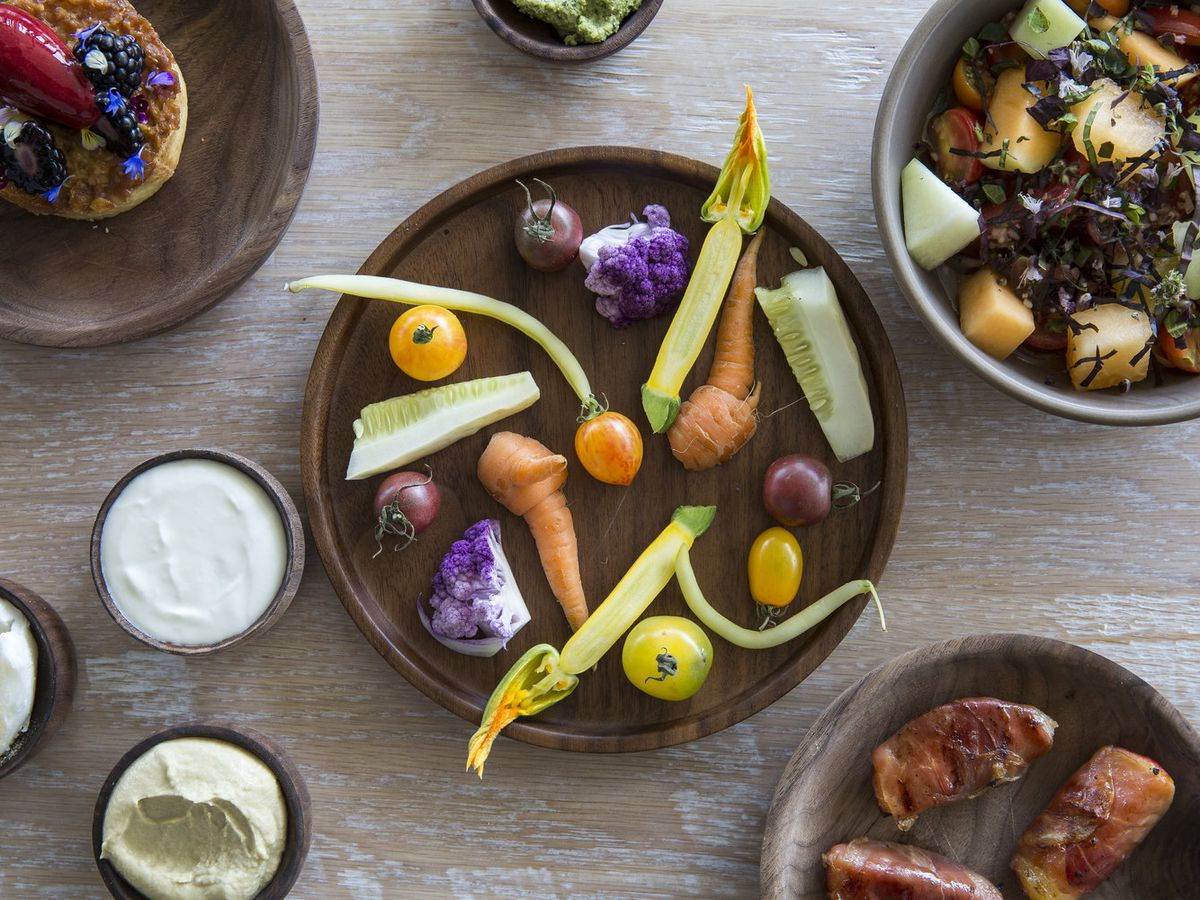 From above, a plate of crudite with dips, a fruit tart, tomato salad, and bacon-wrapped dates