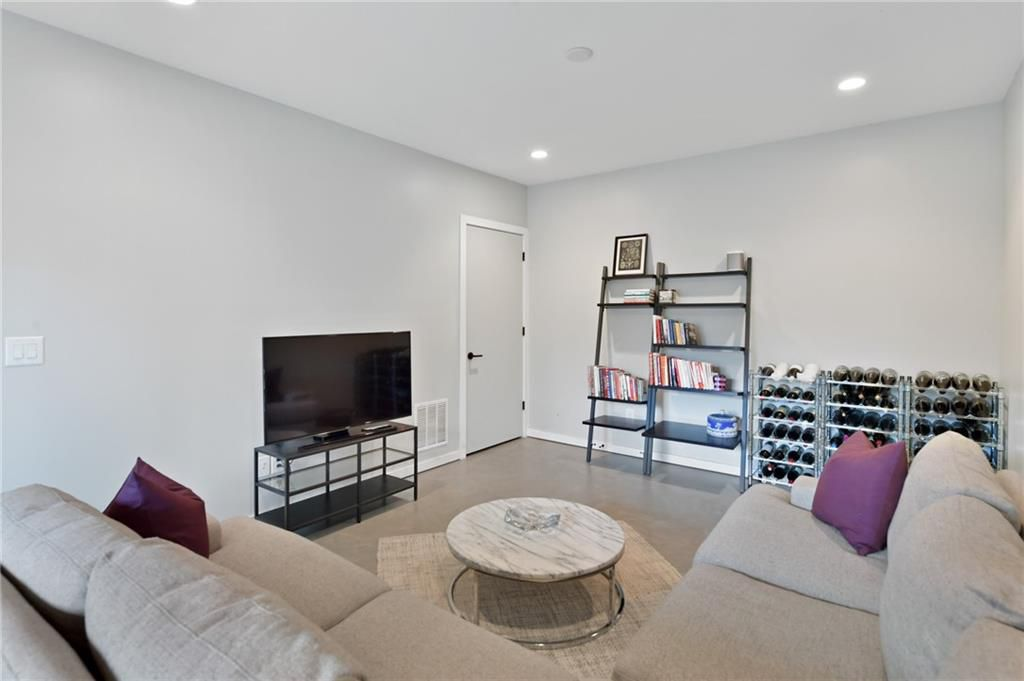 A white room with a TV and beige couch.