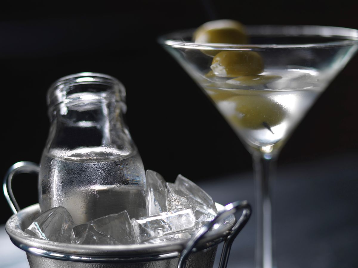A clear martini is in a glass, garnished with green olives. A glass vessel filled with clear liquid sits in a metal ice bucket next to the martini.