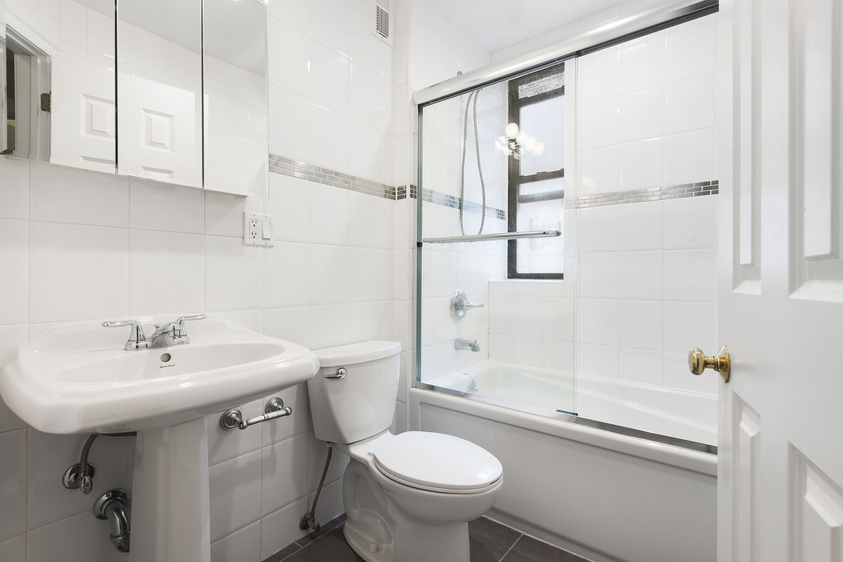 A bathroom with white tiles.