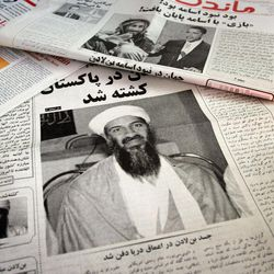 FILE - This May 3, 2011 file photo shows Afghan newspapers in Kabul, Afghanistan headlining the killing of al-Qaida leader Osama bin Laden. The killing of Osama bin Laden, first presented as a moment of national unity by President Barack Obama, has become something else: a political weapon. Obama's re-election campaign is portraying his risky decision to go after America's top enemy as a defining difference with his Republican presidential opponent, suggesting Mitt Romney might not have had the guts to order a mission that put lives and perhaps a presidency at stake.
