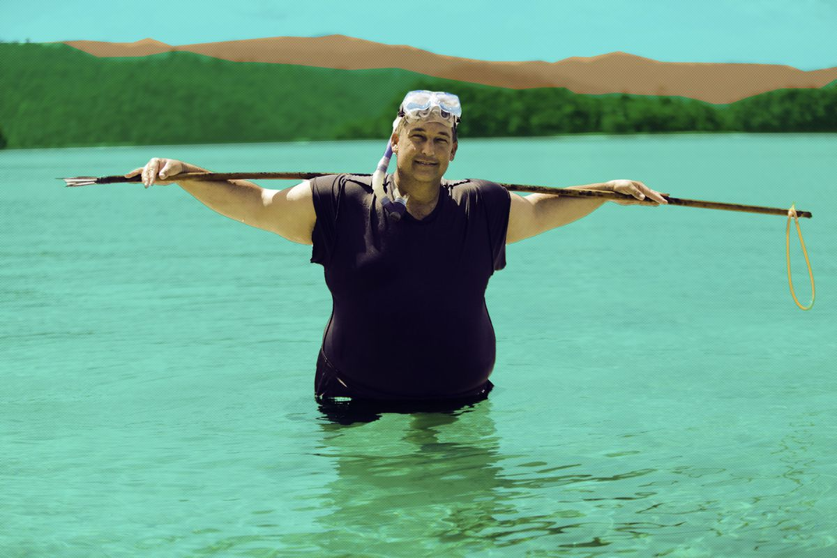 A contestant on 'Castaways' in the water holding a long stick on top of his shoulders