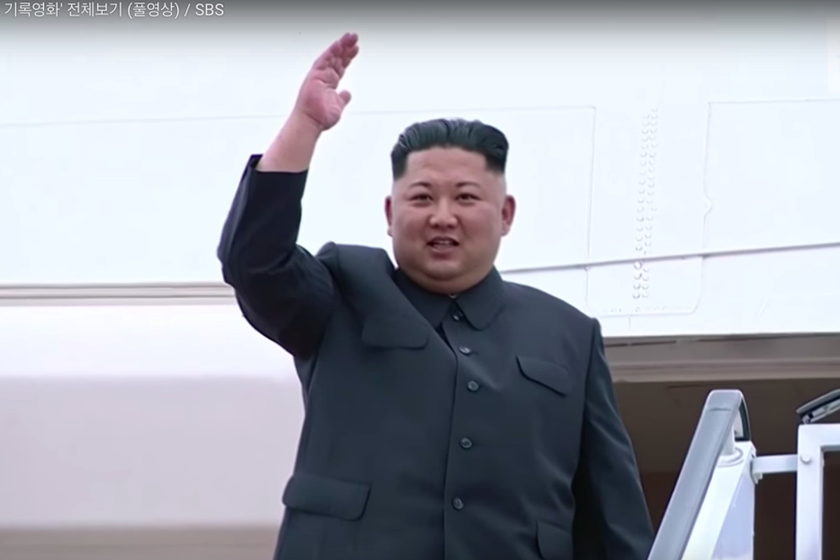 Kim Jong Un waves goodbye as he gets on a plane to Singapore for the summit.