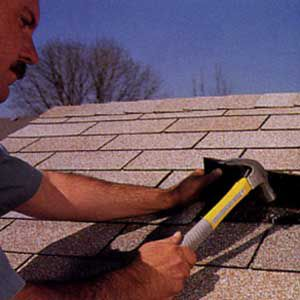 Person using a hammer to put new roof shingle into place.