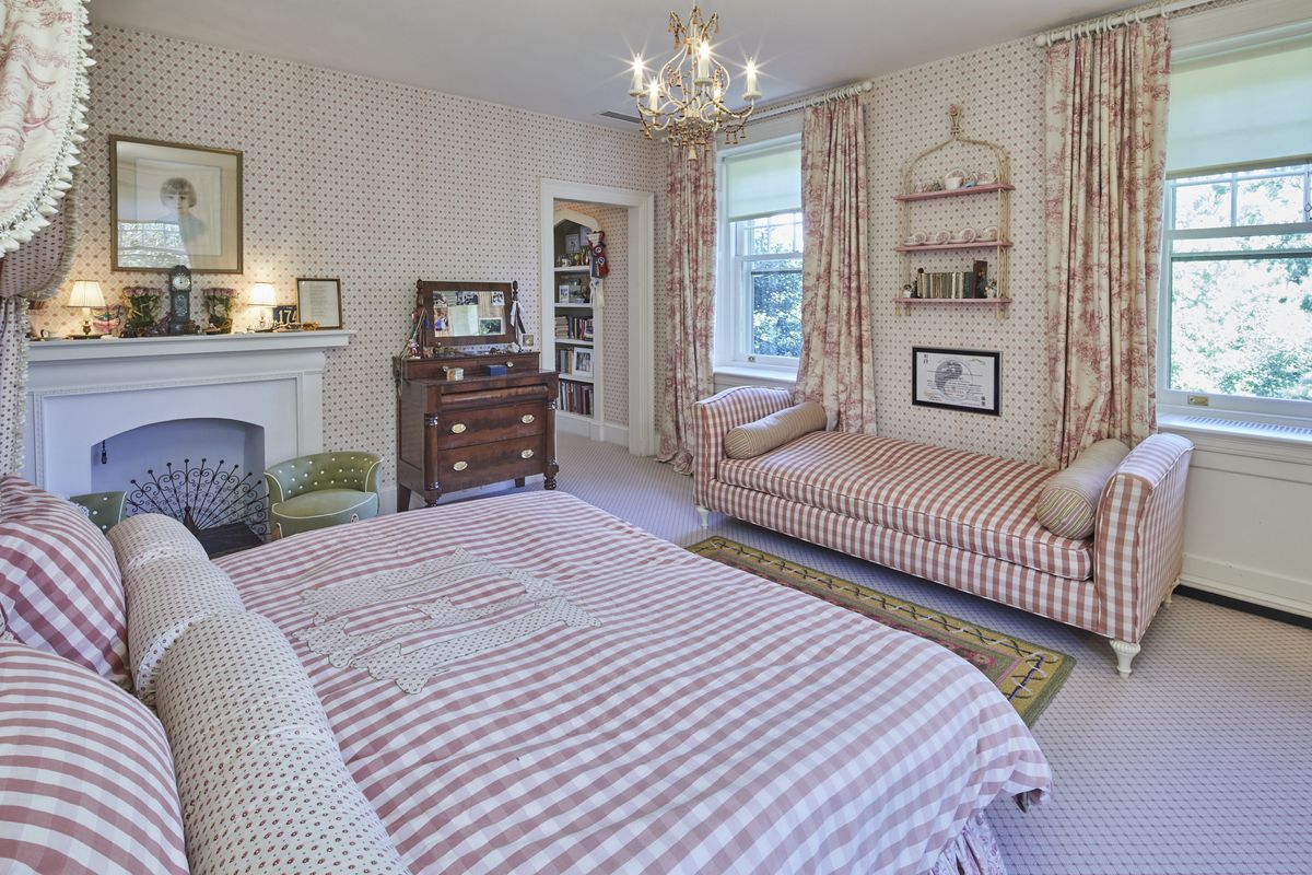 A bedroom features pink gingham bed and bench, with a white fireplace and chandelier.