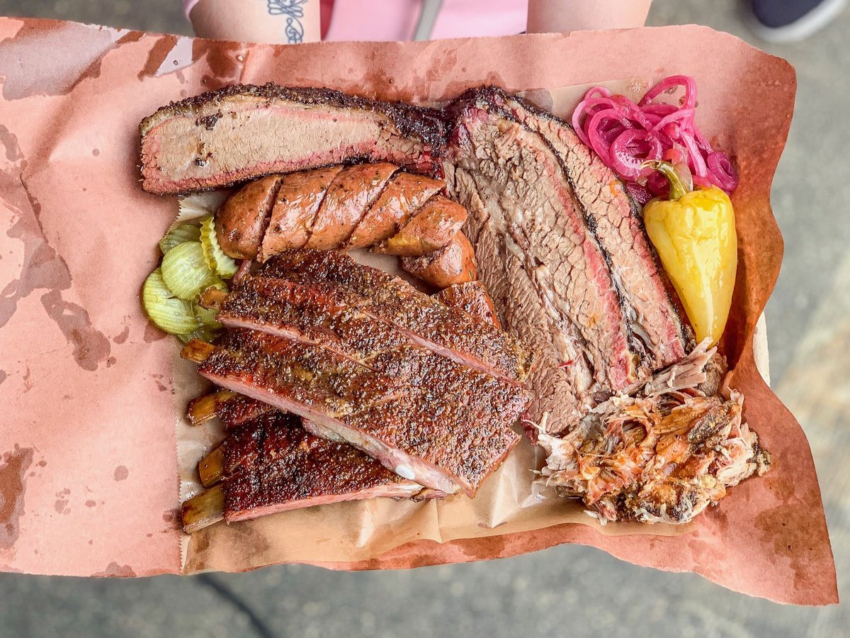 A plate of barbecue, including links and ribs and brisket.