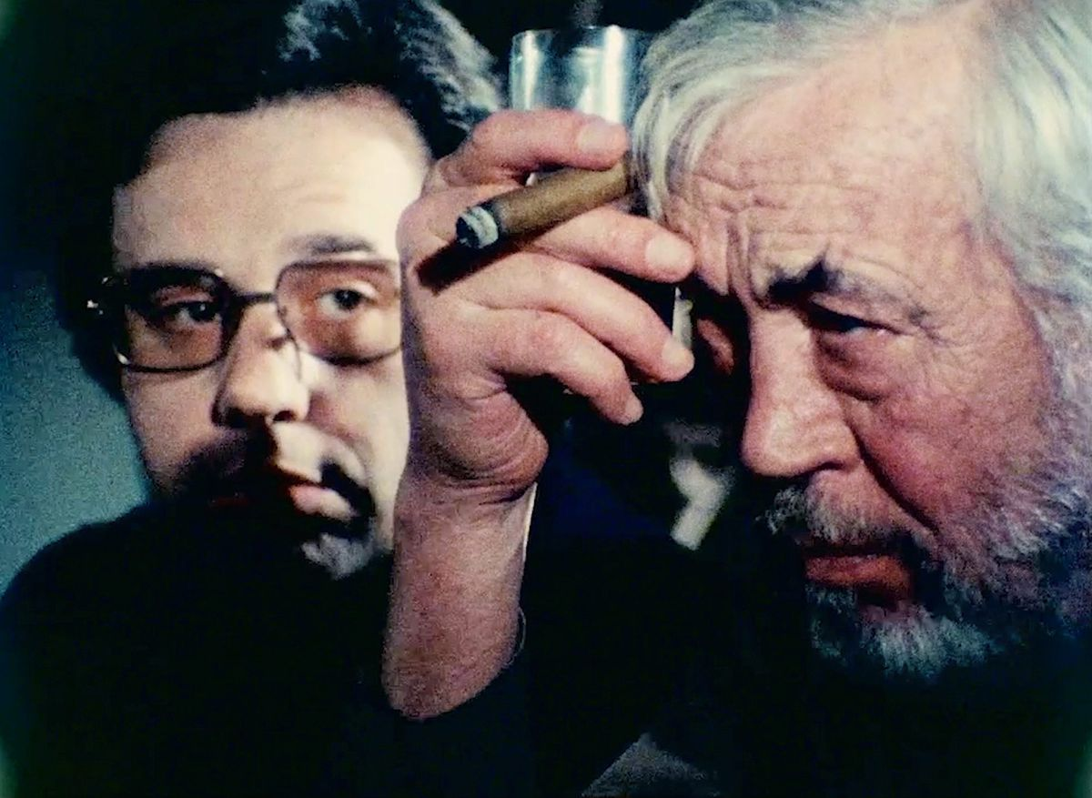 Peter Bogdanovich watches John Huston smoke a cigar in Orson Welles' The Other Side of the Wind