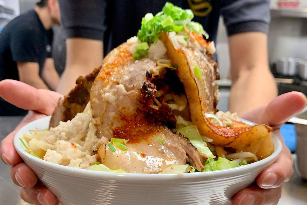 Two hands hold a big white bowl full of ramen, with a mountain of pork belly and other toppings towering up over the top of the bowl