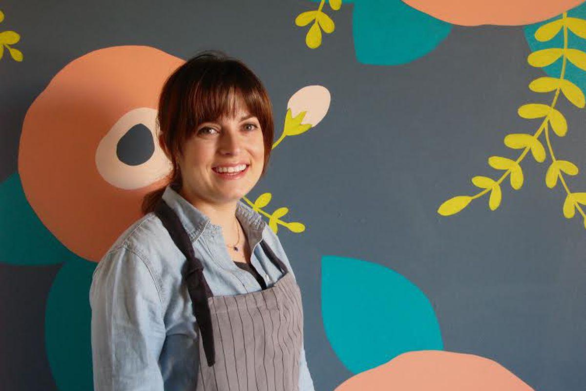 Tova du Plessis in front of Essen Bakery's indoor mural