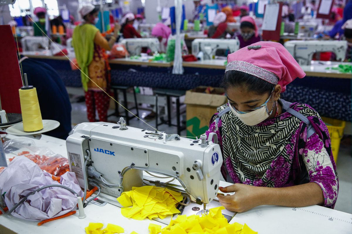 A young woman with a breathing mask over her nose and mouth sits and works at a sewing machine in a garment factory.