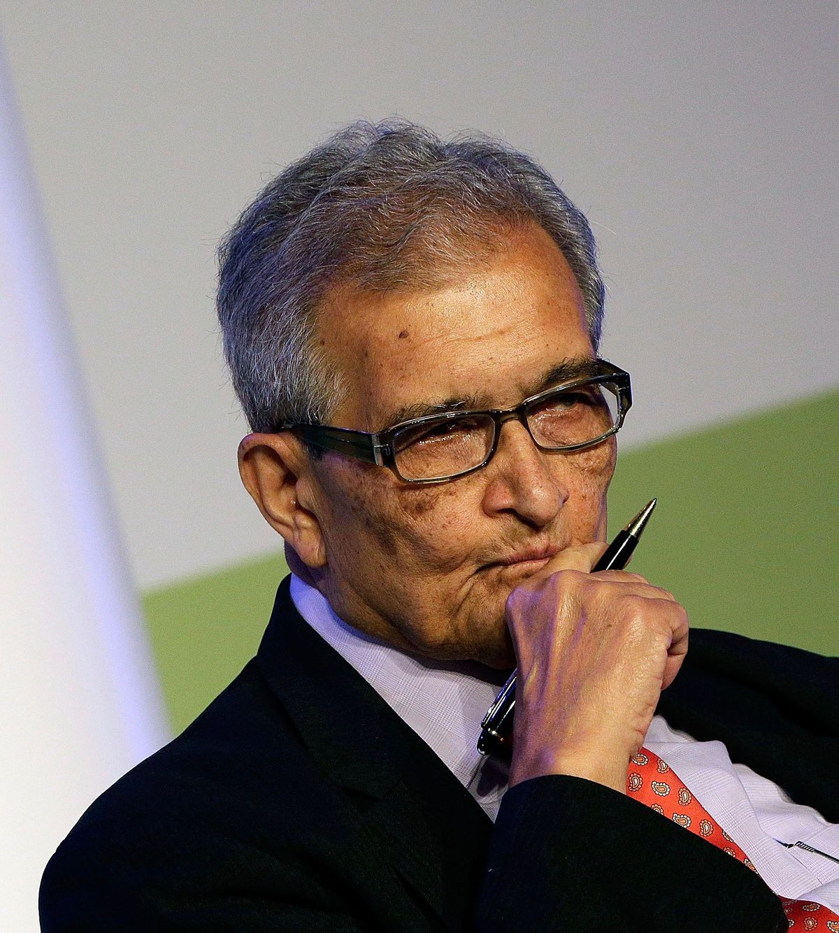 Amartya Sen looks pensive, at a conference.
