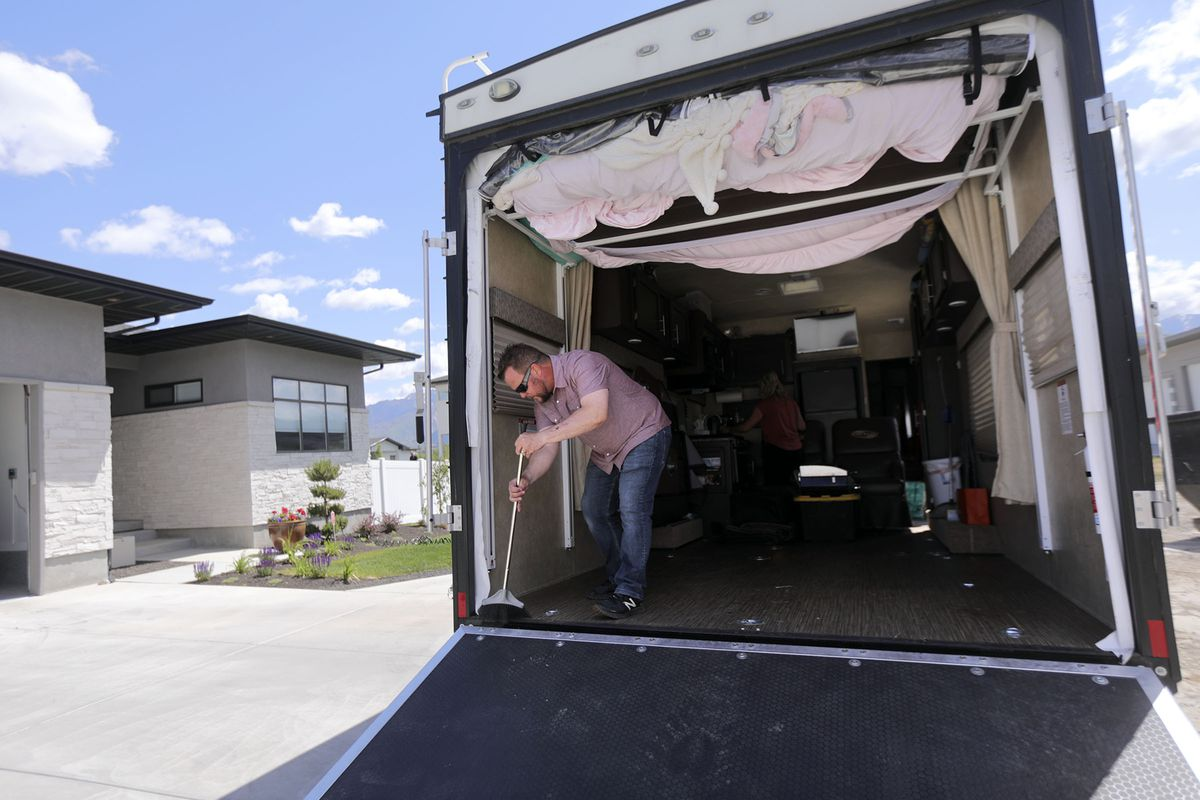 Ryan Frost sweeps out histrailer outside of his home in Draper while prepping for a camping trip to Palisade State Park in Sanpete County on Thursday, May 21, 2020.